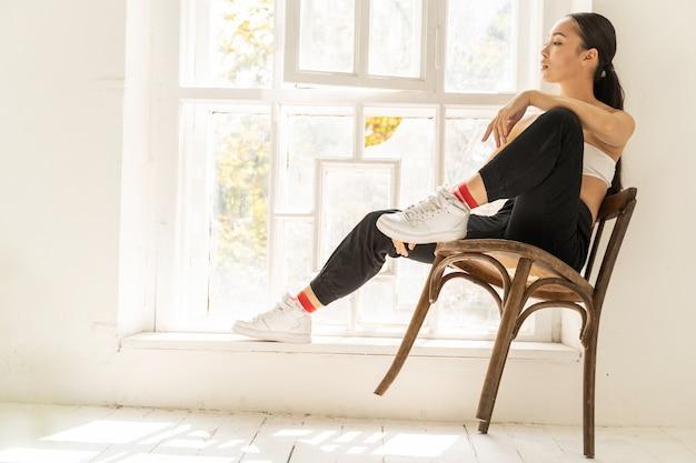 Jeune femme assise près de la fenêtre dans la chambre