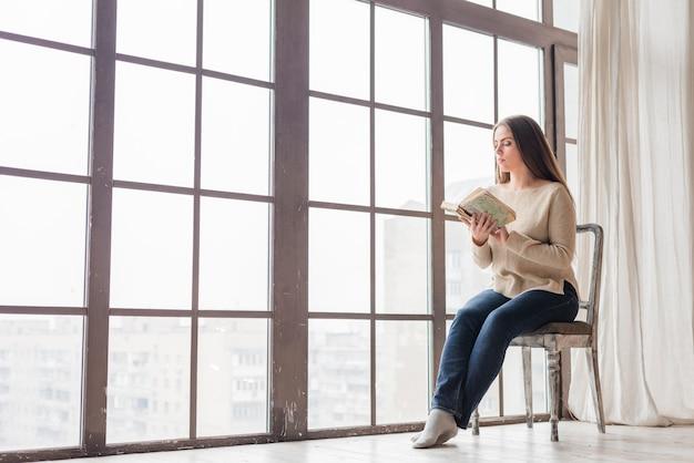 Jeune femme assise près de la fenêtre en lisant le livre