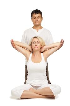Jeune femme assise et recevant un massage d'étirement des bras thaïlandais traditionnel par un thérapeute, isolée sur blanc