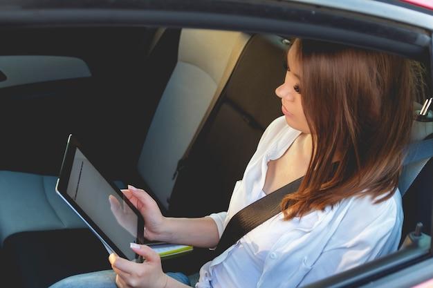 Jeune femme assise sur le siège arrière d'une voiture avec une tablette dans les mains