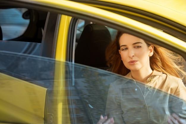 Jeune femme assise sur le siège du passager avant sort de la voiture jaune