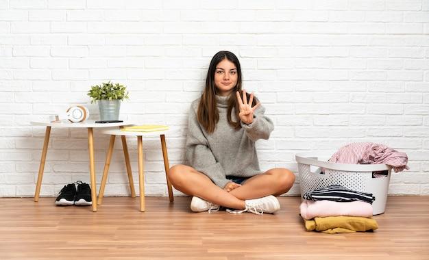 Jeune femme assise sur le sol à l'intérieur avec panier de vêtements heureux et en comptant quatre avec les doigts