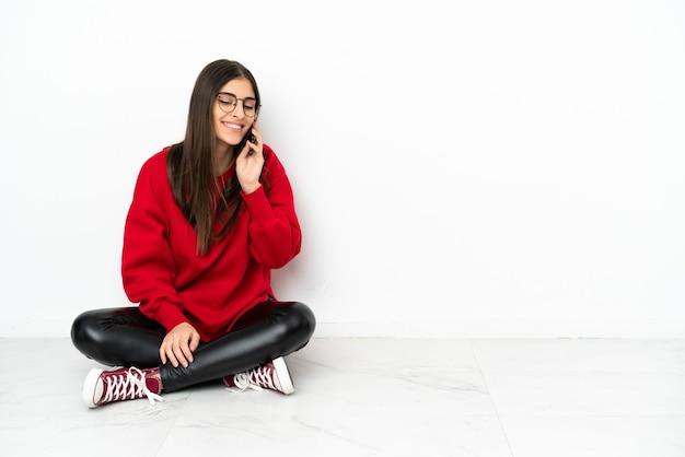 Jeune femme assise sur le sol isolé sur fond blanc en gardant une conversation avec le téléphone portable avec quelqu'un
