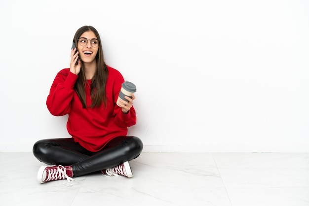 Jeune femme assise sur le sol isolé sur fond blanc tenant un café à emporter et un mobile