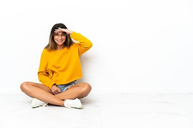Jeune femme assise sur le sol isolé à la recherche de loin avec la main pour regarder quelque chose