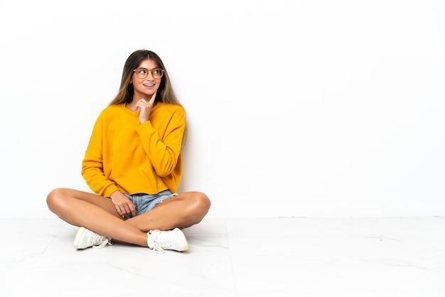 Jeune femme assise sur le sol isolée sur la pensée d'une idée tout en levant
