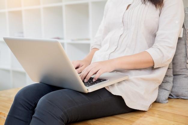 Jeune femme assise sur le sol avec un ordinateur portable dans la bibliothèque, l'éducation et la technologie concept.