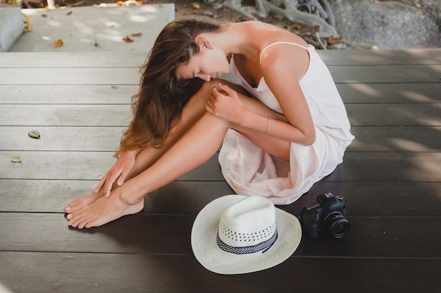 Jeune femme assise sur le sol pieds nus en robe pâle, souriant, beauté naturelle, chapeau de paille, appareil photo numérique,