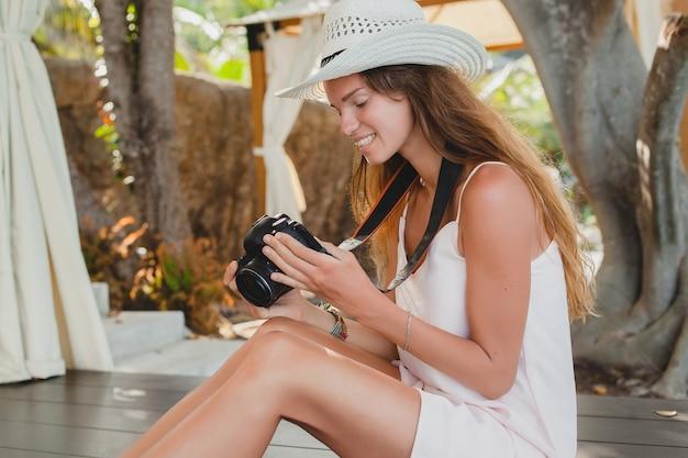 Jeune femme assise sur le sol pieds nus en robe pâle, souriant