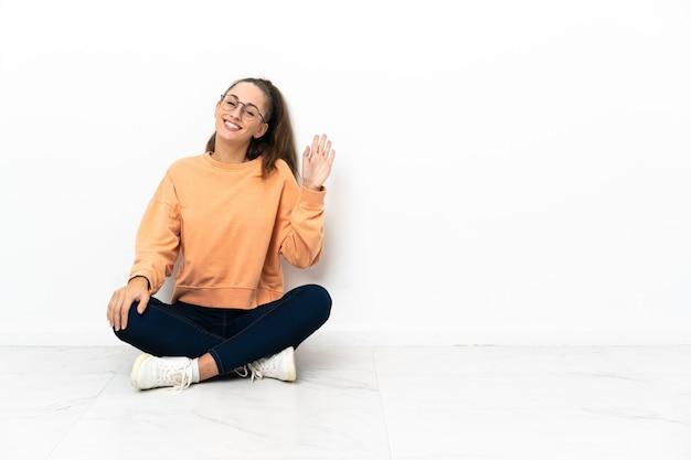 Jeune femme assise sur le sol en saluant avec la main avec une expression heureuse