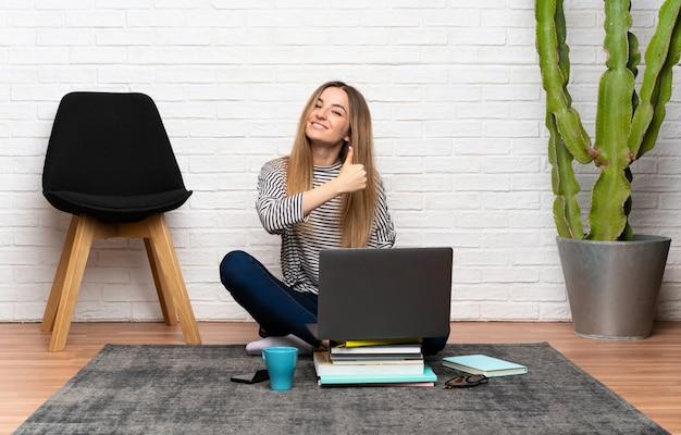 Jeune femme assise sur le sol avec son ordinateur portable donnant un geste du pouce