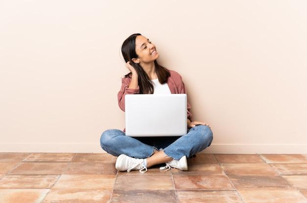 Jeune femme assise sur le sol avec son ordinateur portable