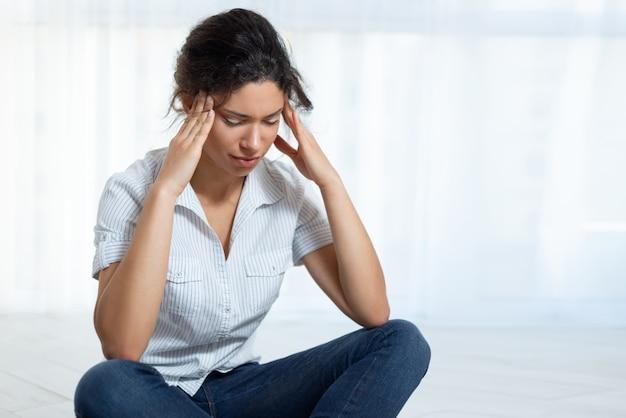 Jeune femme assise sur le sol tenant sa tête ayant un mal de tête