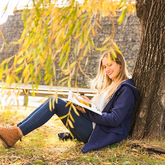 Jeune femme assise sous une branche d'arbre et de la lecture