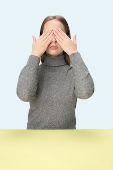 Jeune femme assise à table au studio avec les yeux fermés isolé sur bleu. je ne vois rien