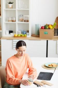 Jeune Femme Assise à La Table Devant Un Ordinateur Portable Et Ouvrant La Boîte Avec De La Nourriture Dans La Cuisine à La Maison Photo Premium