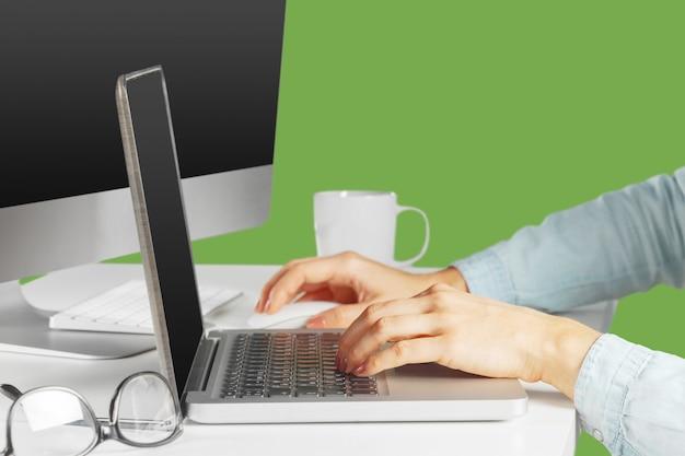 Jeune femme assise à la table avec ordinateur netbook ouvert. personne féminine utilisant la technologie moderne.