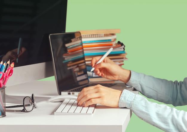 Jeune femme assise à la table avec ordinateur netbook ouvert