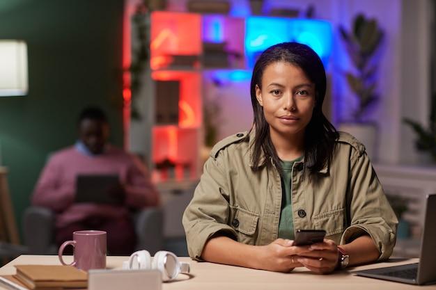 Jeune femme assise à la table et regardant la caméra tout en utilisant son téléphone portable à son travail
