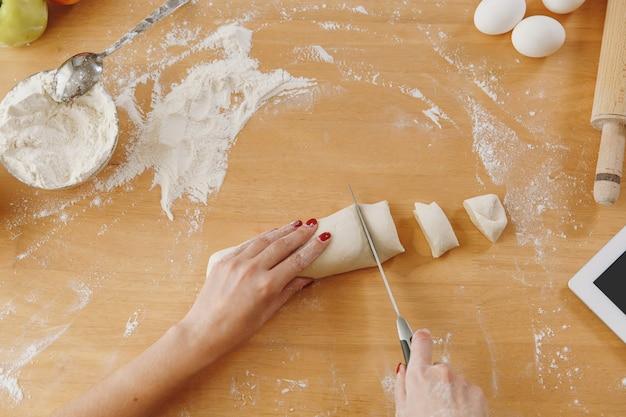 Une jeune femme assise à une table avec une tablette, coupe une pâte avec un couteau en morceaux à la maison dans la cuisine. cuisiner à la maison. préparer la nourriture. vue de dessus.