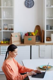 Jeune Femme Assise à La Table Et En Tapant Sur Un Ordinateur Portable Dans La Cuisine, Elle Travaille En Ligne à La Maison Photo Premium
