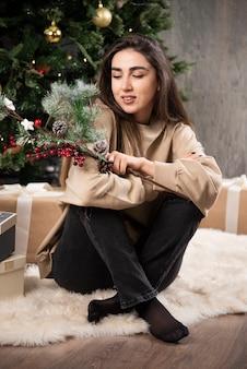 Une jeune femme assise sur un tapis moelleux avec des baies de houx de noël .
