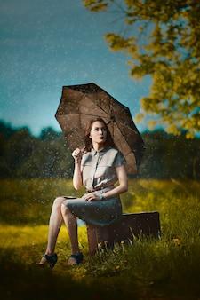 Jeune femme assise sur une valise sous la pluie et en attente