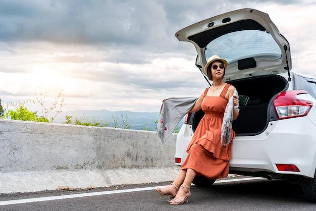 Jeune femme assise sur la voiture arrière par temps nuageux