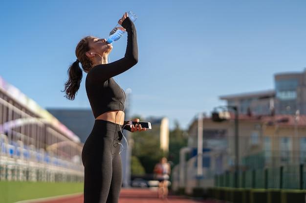 Jeune femme assoiffée en forme d'eau potable à partir d'une bouteille en plastique