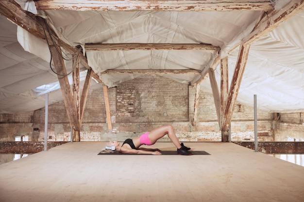 Une jeune femme athlétique en chemise et casque blanc travaillant à écouter de la musique sur un chantier de construction abandonné. élongation. concept de mode de vie sain, sport, activité, perte de poids.
