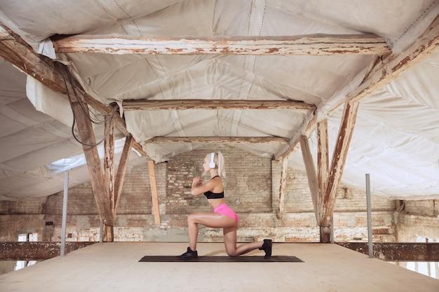 Une jeune femme athlétique en chemise et casque blanc travaillant à écouter de la musique sur un chantier de construction abandonné. faire des squats. concept de mode de vie sain, sport, activité, perte de poids.