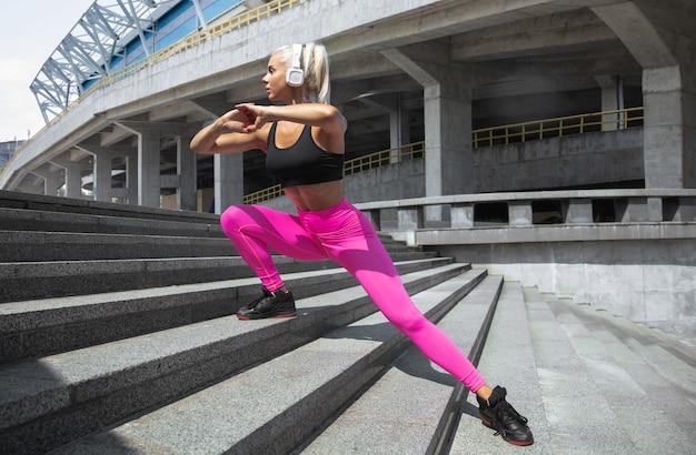 Une jeune femme athlétique en chemise et casque blanc travaillant à écouter de la musique dans la rue à l'extérieur. faire des fentes dans les escaliers. concept de mode de vie sain, sport, activité, perte de poids.