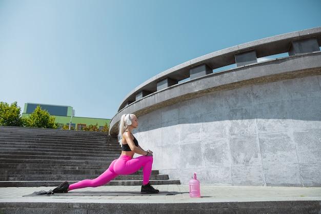 Une jeune femme athlétique en chemise et casque blanc travaillant à écouter de la musique dans la rue à l'extérieur. faire des fentes et des étirements. concept de mode de vie sain, sport, activité, perte de poids.
