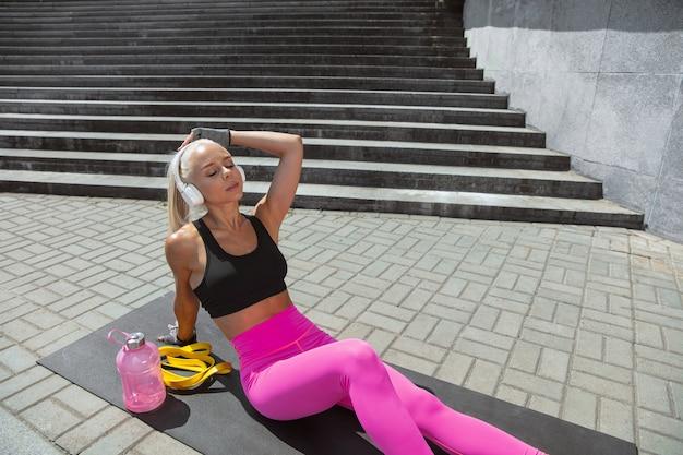 Une jeune femme athlétique en chemise et casque blanc travaillant à écouter de la musique dans la rue à l'extérieur