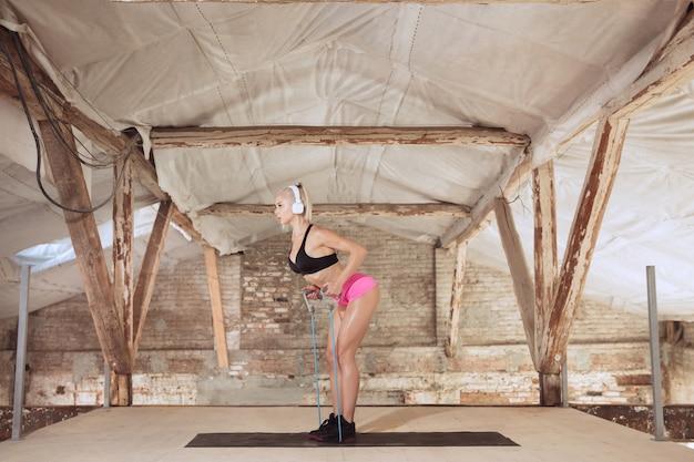 Une jeune femme athlétique dans un casque blanc travaillant à écouter de la musique sur un chantier de construction abandonné. faites de l'exercice avec la corde. concept de mode de vie sain, sport, activité, perte de poids.