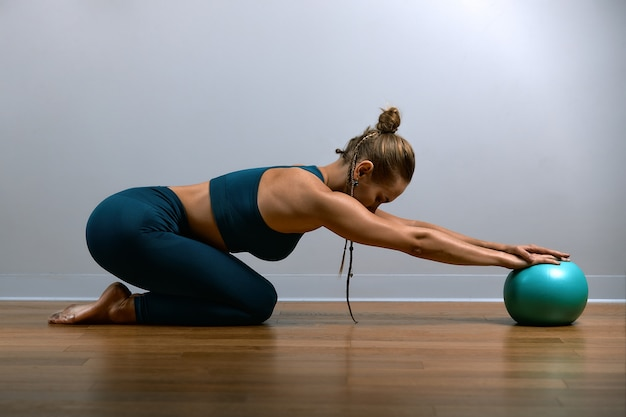 Jeune femme athlétique, faire des exercices sur fitball dans la salle de gym
