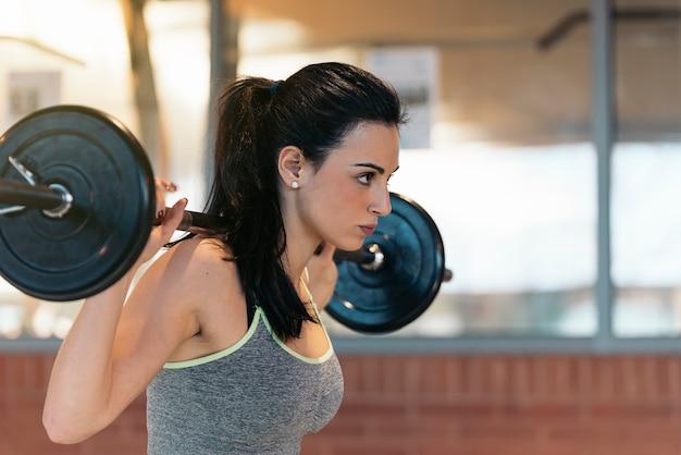 Jeune femme athlétique faisant du sport dans la salle de gym