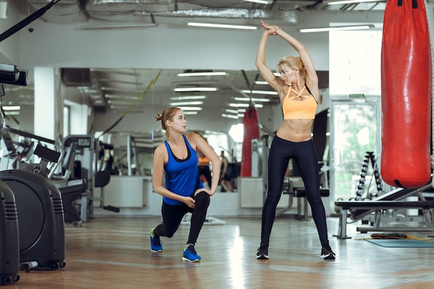 Jeune femme athlétique faisant des exercices avec un entraîneur personnel
