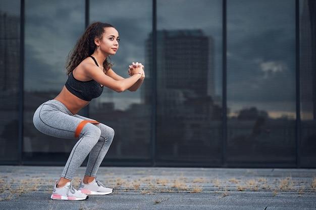 Jeune femme athlétique faisant des exercices de squats avec du caoutchouc de sport à l'emplacement de la ville urbaine