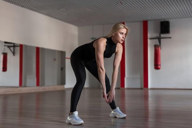 Jeune femme athlétique mince dans des vêtements à la mode noir sportif sur une formation dans la salle de gym