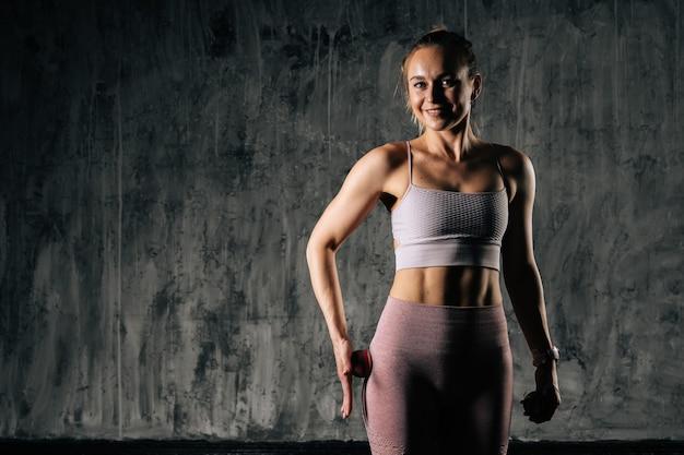 Jeune femme athlétique musclée avec un beau corps parfait portant des vêtements de sport à l'aide d'une petite balle de massage sur la jambe. femme de remise en forme caucasienne qui pose en studio avec un fond gris foncé.