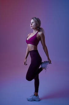 Jeune femme athlétique avec des poses de corps parfaits en studio, fond néon