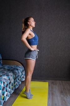 Jeune femme athlétique pratiquant le yoga, l'étirement du corps, l'exercice, l'entraînement, portant des vêtements de sport, un t-shirt bleu, un short, près du canapé à la maison