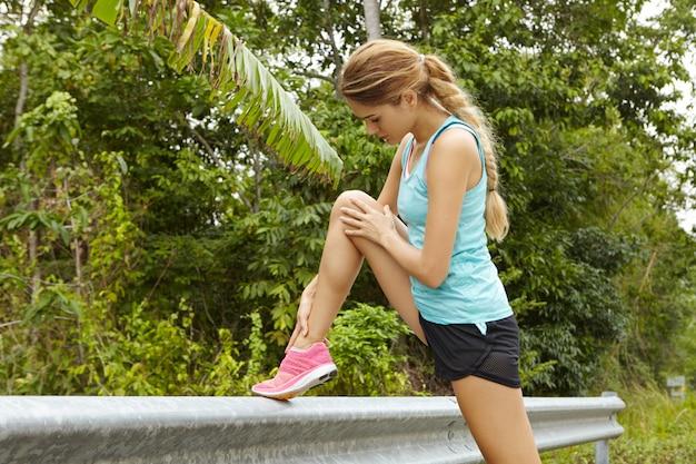 Jeune femme athlétique qui s'étend avant le matin en cours d'exécution à l'extérieur.