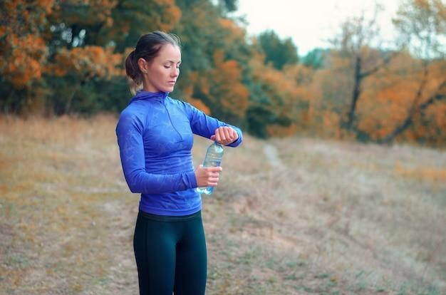 Une jeune femme athlétique de race blanche dans une veste de sport bleue avec une capuche et des leggins noirs ouvre une bouteille avec de l'eau après le jogging