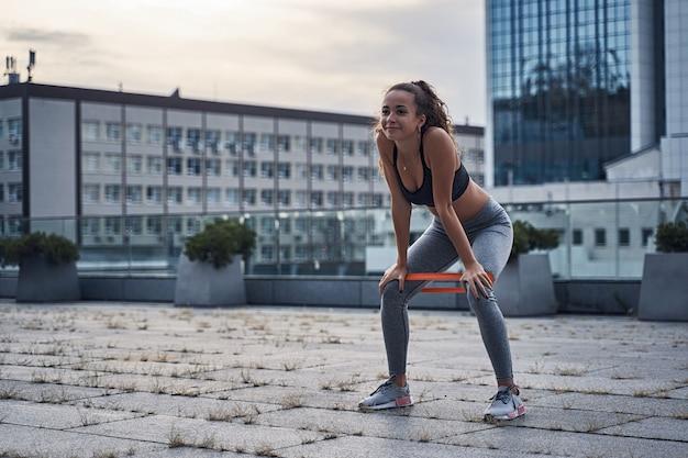 Jeune femme athlétique souriante tout en faisant des exercices de squats avec du caoutchouc de sport dans la ville urbaine