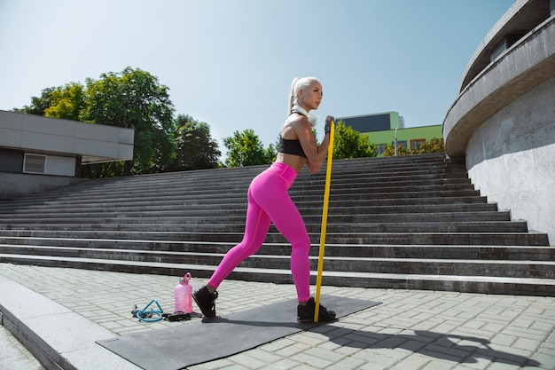Une jeune femme athlétique travaillant dans la rue de la ville