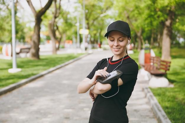 Jeune femme athlétique en uniforme noir avec des écouteurs écoutant de la musique, regardant sur un téléphone portable à l'aide d'une application, une application pour courir ou faire du jogging, s'entraîner dans un parc de la ville à l'extérieur