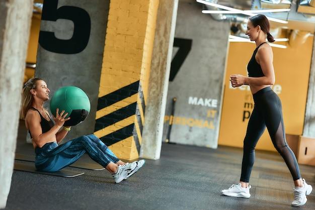 Jeune femme athlétique en vêtements de sport s'exerçant avec un ballon de fitness au gymnase avec l'aide de personnel