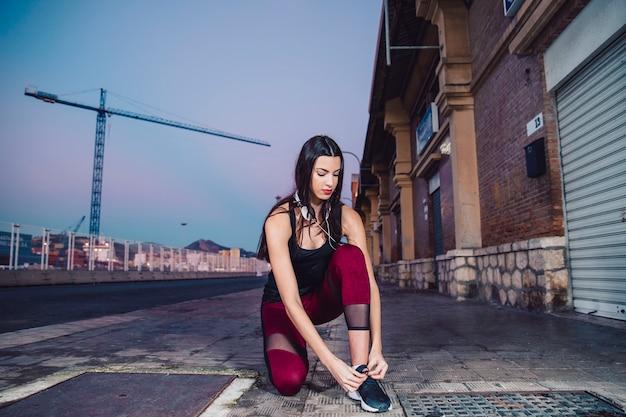 Jeune femme attachant des lacets pendant l'entraînement
